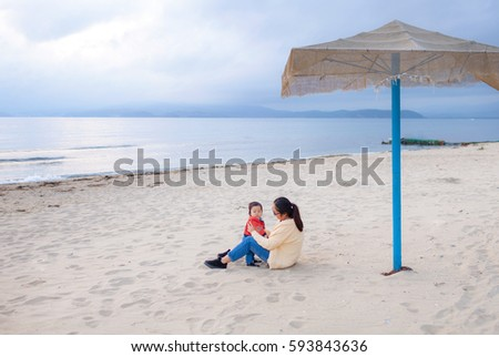 Mother and son meet the sunset on the beach. A family #593843636