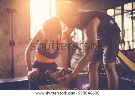 Sporty girl doing weight exercises with assistance of her personal trainer at public gym. Royalty-Free Stock Photo #593846600