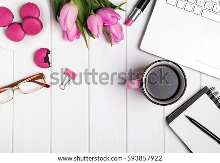 Woman's desktop with laptop, notepad, glasses, coffee and tulips. Top view #593857922