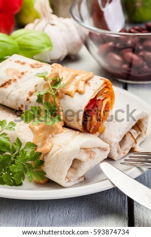Mexican burritos wraps with mincemeat, beans and vegetables on a plate #593874734
