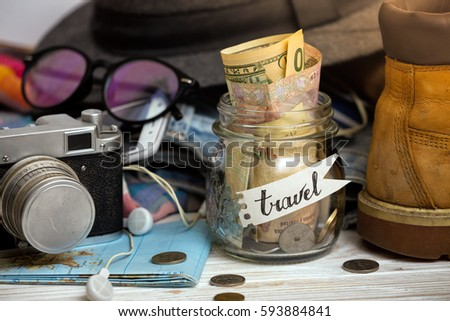 wanderlust. adventure concept. background - what to take for a trip - camera, smartphone, jar with money, glasses, shoes, jeans, accessories