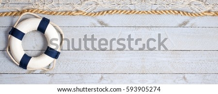 Lifebuoy on wooden background texture with rope and fishing net, copy space for individual text Royalty-Free Stock Photo #593905274
