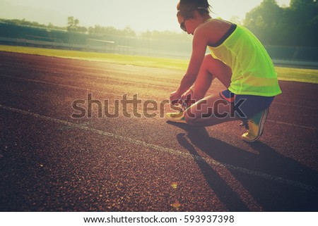 young fitness woman runner tying shoelace on stadium track #593937398