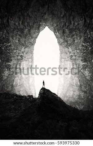 Huge cave entrance with man silhouette on cliff, surreal underground landscape