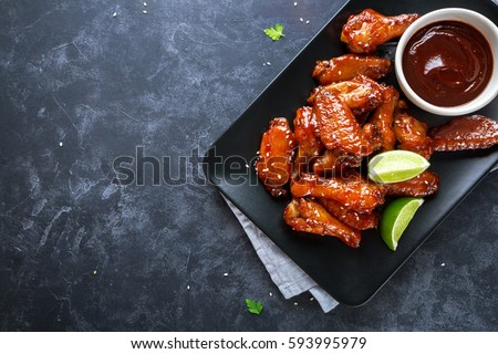Baked chicken wings with sesame and sauce. Food background with copy space. Top view Royalty-Free Stock Photo #593995979