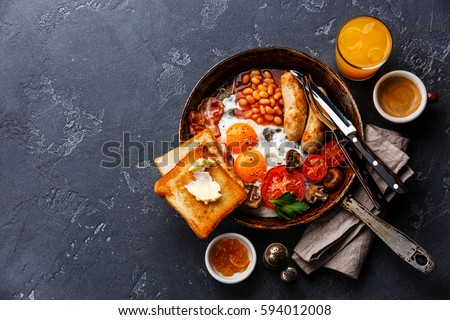 English Breakfast in cooking pan with fried eggs, sausages, bacon, beans, toasts and coffee on dark stone background copy space #594012008