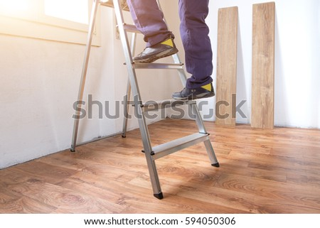 Feet of a carpenter  ready for work on a ladder #594050306