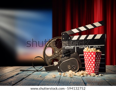 Retro film production accessories placed on wooden planks. Concept of film-making. Red curtain and movie screen on background #594132752