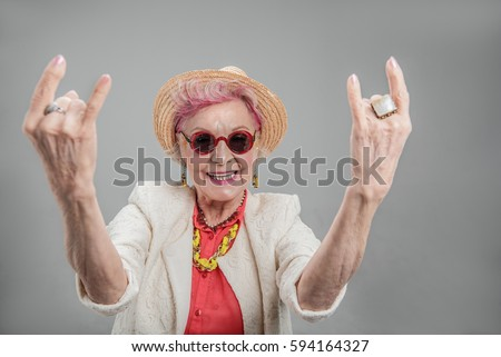 Cheerful senior woman posing in studio