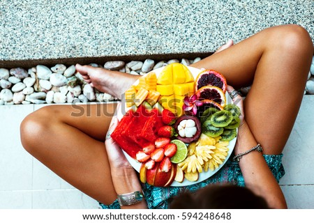 Girl relaxing and eating fruit plate by the hotel pool. Exotic summer diet. Photo of legs with healthy food by the poolside, top view from above. Tropical beach lifestyle. #594248648