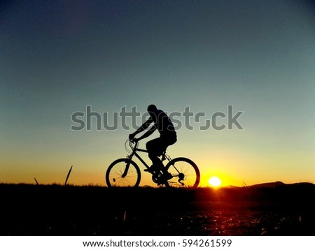 Cyclist on bike during sunset #594261599