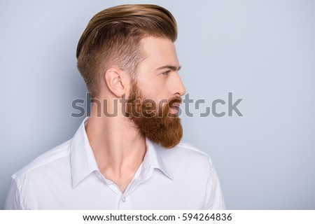Side view portrait of confident bearded man with beautiful hairstyle   in white shirt looking on copy space Royalty-Free Stock Photo #594264836