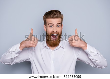 Portrait of excited happy bearded man showing thumb up sign and open mouth