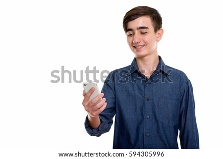 Studio shot of young happy Persian teenage boy smiling while using mobile phone isolated against white background #594305996