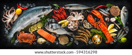 Fresh fish and seafood arrangement on black stone background Royalty-Free Stock Photo #594316298