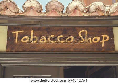 Tobacco Shop, wooden sign at the entrance in tobacco shop. Vintage style. Royalty-Free Stock Photo #594342764