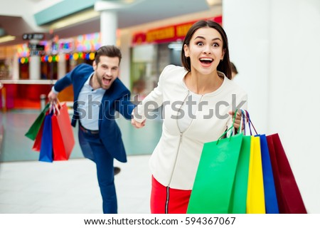 It's shopping and fun  time. Portrait of cheerful  successful happy young lovely couple holding  colored shopping bags and laughing in mall. Concept of consumerism, sale, rich life. #594367067