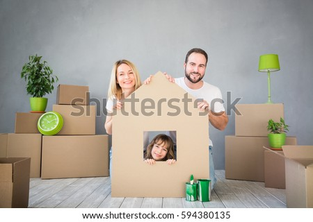 Happy family playing into new home. Father, mother and child having fun together. Moving house day and real estate concept #594380135