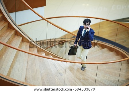 Portrait of modern businessman wearing stylish formal suit going up spiral staircase in designer office building calling by smartphone #594533879