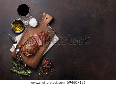 Grilled ribeye beef steak with red wine, herbs and spices. Top view with copy space for your text #594607136