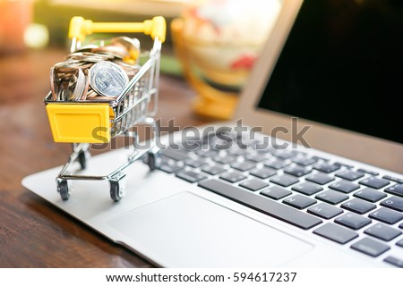 Small shopping cart contains coins on laptop and working space on wooden table in Coffee shop using as shopping online or marketing technology background concepts #594617237