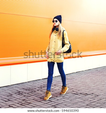 Fashion pretty blonde woman walking in city over orange colorful background #594650390
