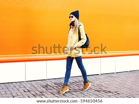 Fashion pretty blonde woman walking in city on a orange colorful background  #594650456