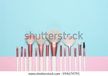Set of makeup brushes on pink and aqua colored composed background. Top view point, flat lay. #594674795