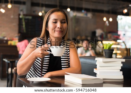 Asian woman relaxing and reading a book in the cafe. Women lifestyle concept. #594716048