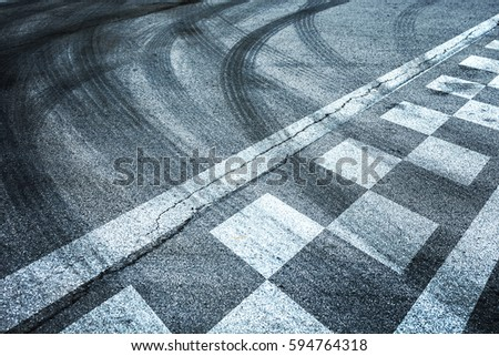 Finish and start pattern line racing on the asphalt road background with crossing of tires tracks. #594764318