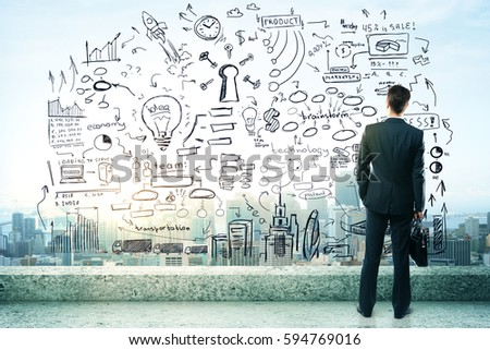 Thoughtful young businessman on rooftop with abstract business sketch. City view in the background. Success concept #594769016