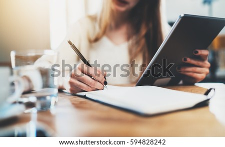 Closeup of female hand making notes in notebook and using modern digital tablet at home interior, businesswoman working at office via tablet pc, female student studying at library, flare light Royalty-Free Stock Photo #594828242
