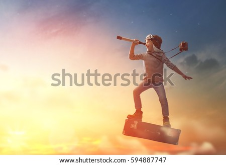 Dreams of travel! Child flying on a suitcase against the backdrop of sunset. Royalty-Free Stock Photo #594887747