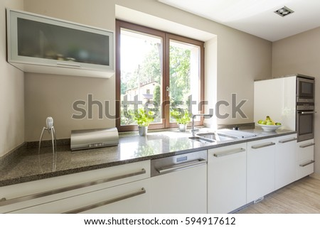 Kitchen in bright colors with window, cupboards, sink and modern eguipment #594917612