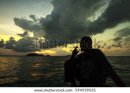 Tioman , Malaysia - April 24, 2015 : An old Malay man smooking on open water from the boat. Beautiful  sunset in the background at Tioman Island , Malaysia. #594939035