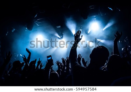 Raised hands of fans during a concert (show or performance) on the background of blue rays of light  #594957584