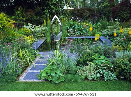 Blue, grey and yellow flowers in a colorful water garden #594969611