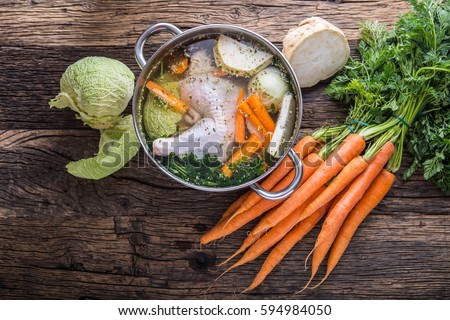 Top view of chicken soup -  broth on wooden table with vegetable.