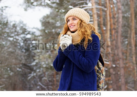 Beautiful young girl in blue jacket and with bag on her back and drinking tea. Travel girl. #594989543