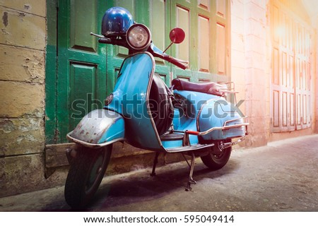 Vintage scooter stands in an alley. Post process in vintage styl #595049414