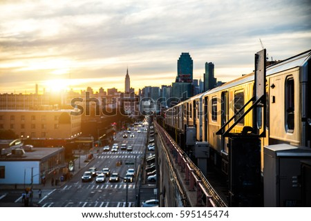 Subway train in New York at sunset and Manhattan cityscape view #595145474