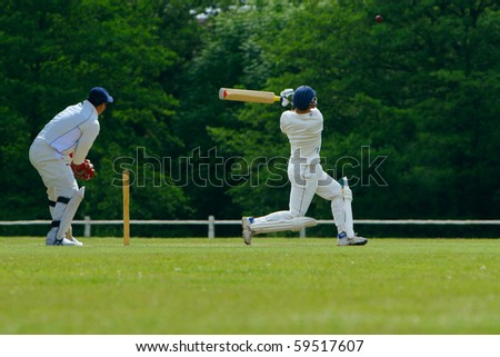 A cricket batsman playing a pull shot towards the boundary in a cricket match while the catcher looks on.