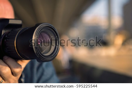 Photographer shooting with a DSLR camera. The camera is on the foreground. #595225544