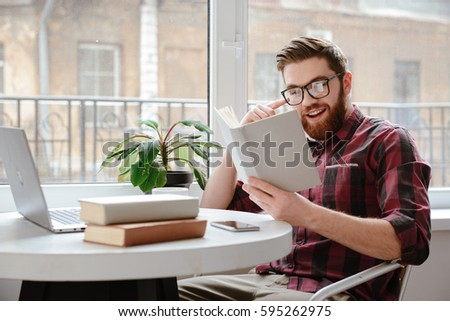 Image of happy bearded young man student wearing glasses sitting in cafe while reading books. #595262975