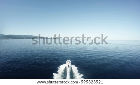 Aerial flight bird view behind fancy speedboat moving fast over quiet flat sea very beautiful day white fast ship moving straight over blue water in background showing shore island and blue sky 4k Royalty-Free Stock Photo #595323521