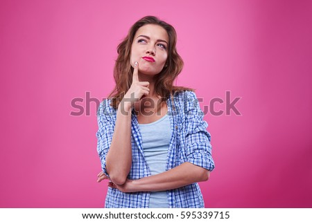 Studio portrait of beautiful young woman thinking and looking upwards. The concept of perception and reflection 