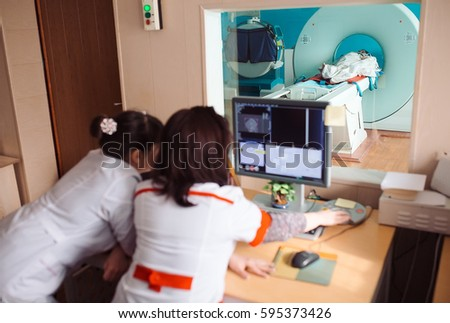 MRI machine and screens with doctor and nurse #595373426