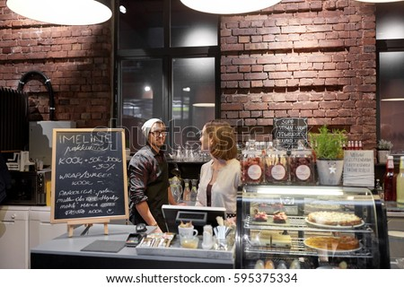 small business, people and service concept - happy bartenders at cafe or coffee shop counter #595375334
