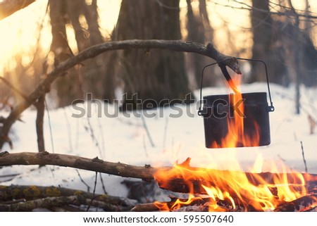 A pot in the fire, water is heated in the winter forest a #595507640