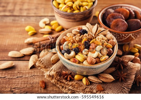 Mix of nuts and dried fruits on a old rustic table. Gold pistachios, cashews, hazelnuts, almonds. #595549616